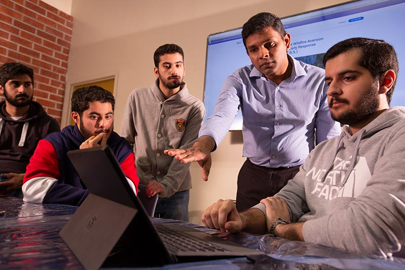 CSUF Award winning drone team working at computer.