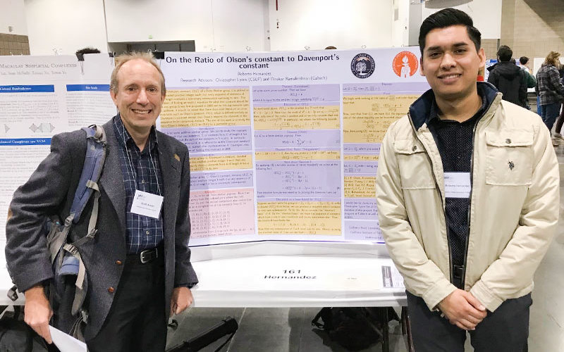 Scott Annin and Roberto Hernandez standing in front of their Olson's and Davenport's Constant research paper.