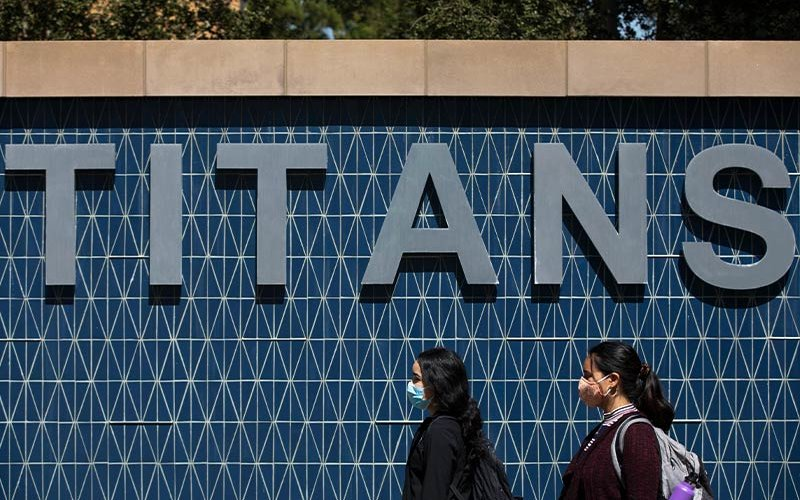 Masked students in front of Titans sign.