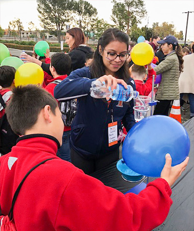 CSUF student demonstrates how electricity works with elementary school children.