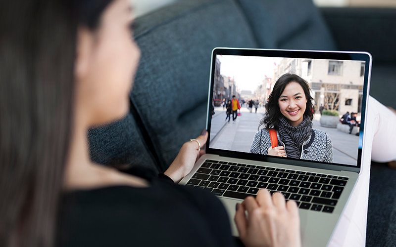 Student with laptop studying abroad virtually learning Korean.