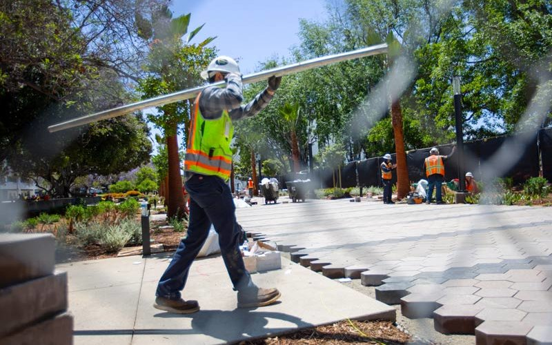 Worker with construction material walks over new promenade.