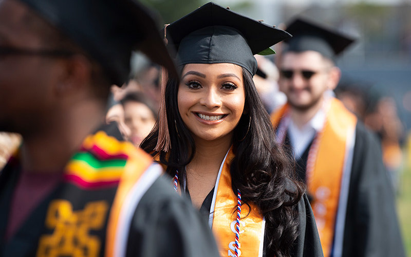 Graduate smiling in commencement line.