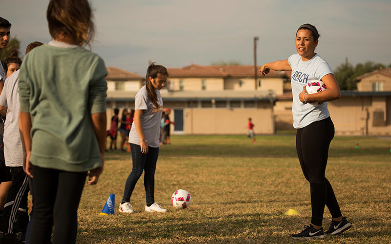 Student leads soccer exercise routine.