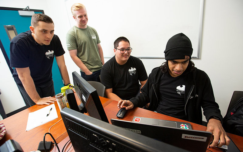 Student Shripal Rawal, right, and other cybersecurity students work on computer.