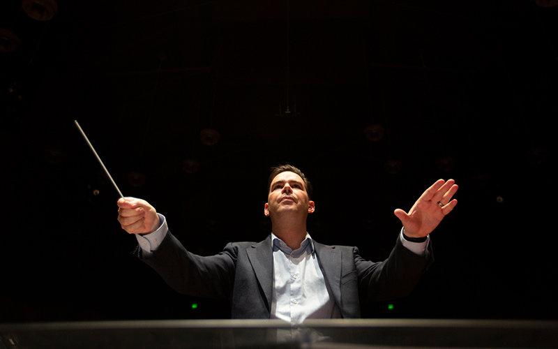 Dustin Barr conducting at podium.