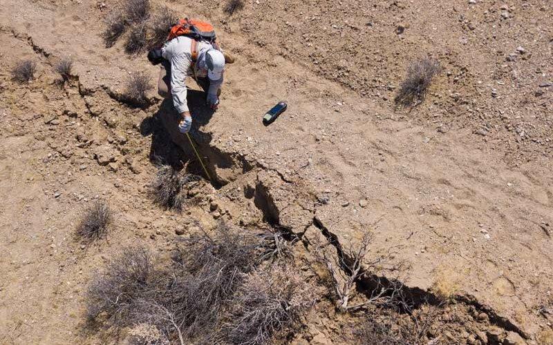 Earthquake researcher Sinan Açkiz studies a surface rupture.