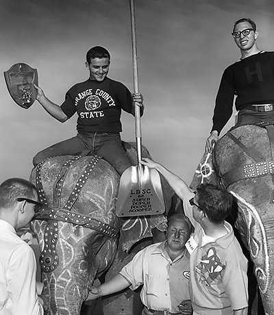 Man on an elephent holds a plaque and a college student hands a shovel to him.