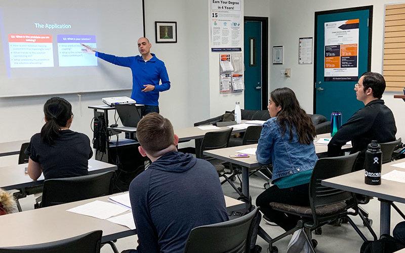 Atul Teckchandani teaching in classroom.
