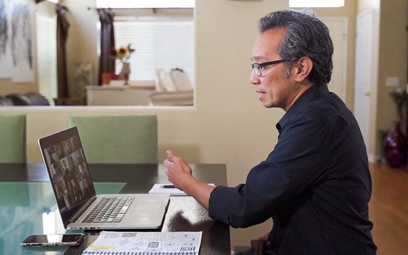 Fernando Del Rosario working on laptop.