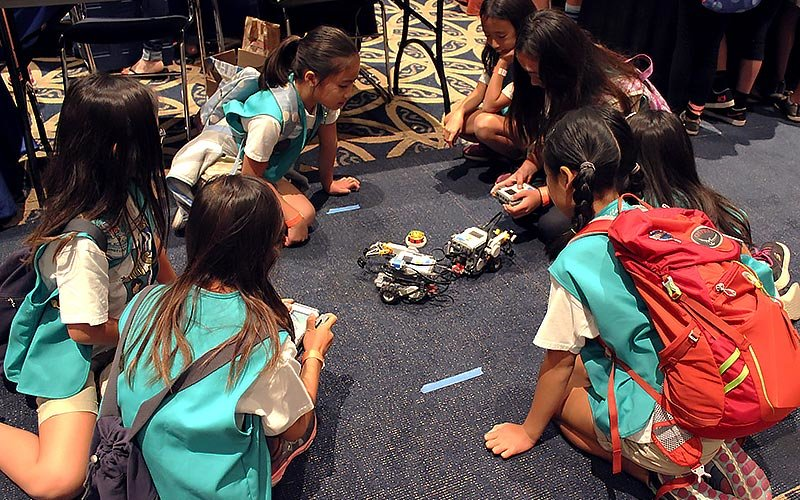 GIrl scouts observing robots.