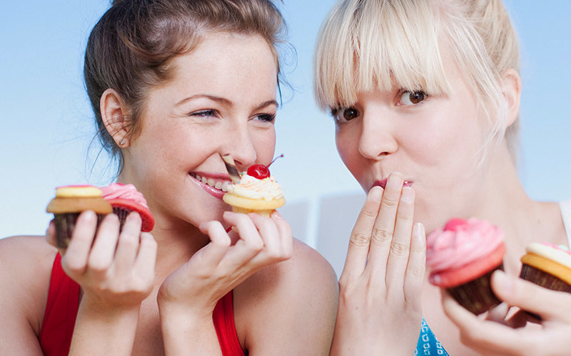 Two women eating cake by the ocean.