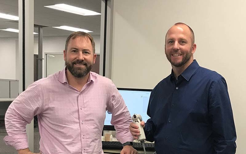 Szolomayer (right) holds a new Lantos Technologies 3D ear scanner. Brian Fligor, chief audiology officer for Lantos, is at left.