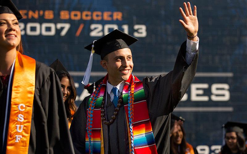 Hispanic graduate waving at commencement.