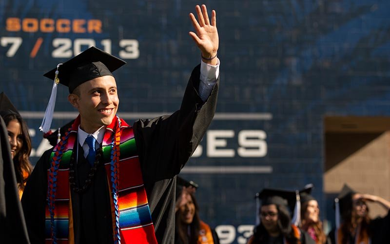 Hispanic graduate waves to his family in the stadium.