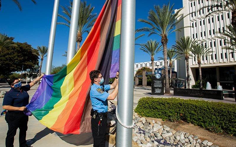 LGBTQ flag raises on campus.