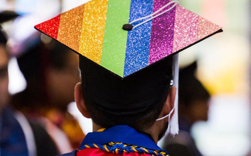LGBTQ Graduate with rainbow inspired cap.