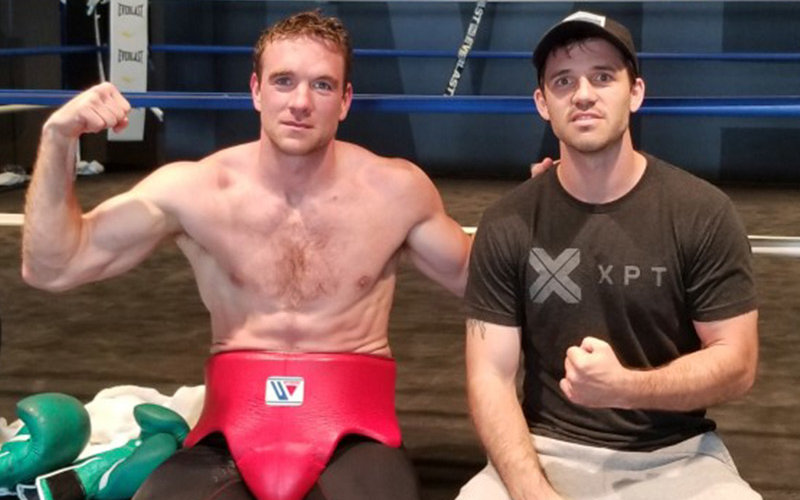 Mike Lee and Andy Galpin flex in a gym.
