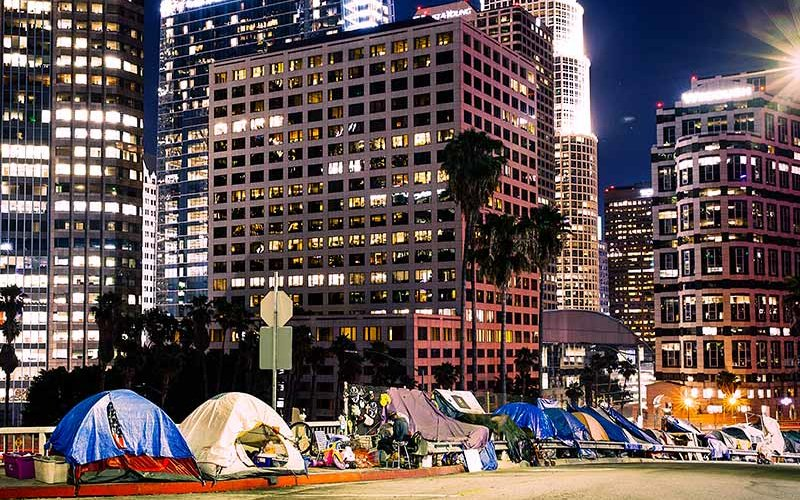 A homeless encampment in front of the Los Angeles Skyline.