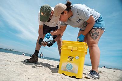 Students pick up trash along beach.
