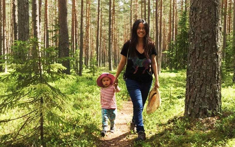 Nga Nguyen walking through forest with child.