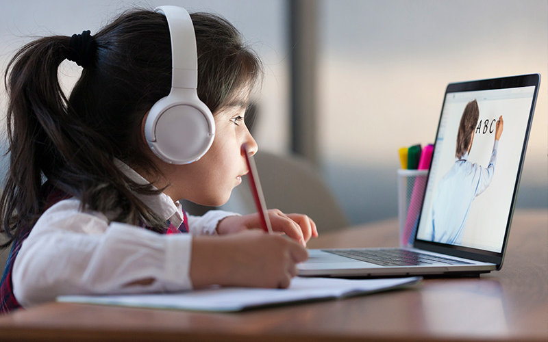 Child learns online with laptop.