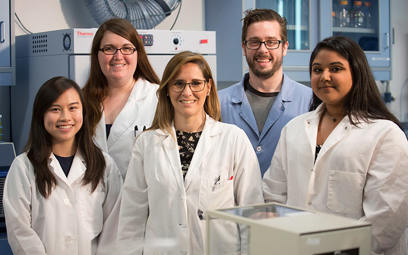 Professor and four of her students posing insider her parasite research lab
