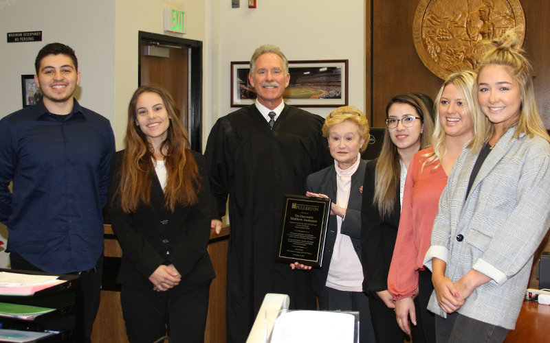Students visit with Judge in courtroom.