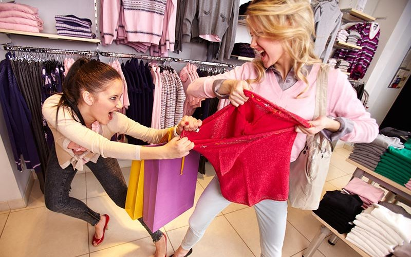 Customers fighting over garment in store.