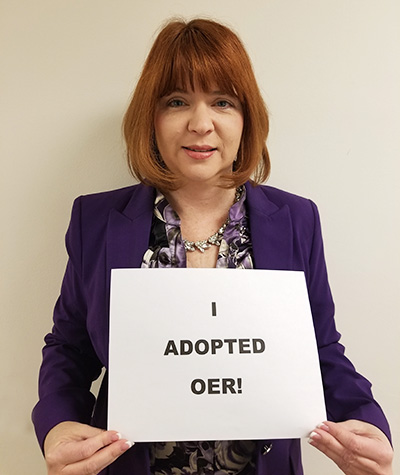 Shelli Wynants holding sign 'I Adopted OER!'