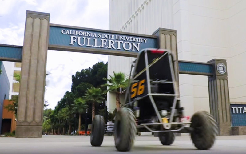 President Virjee Drives a Baja Racer on campus during the student convocation.