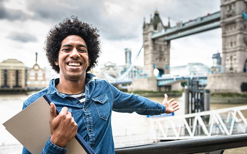 African American student poses in front of the Tower Bridge in London