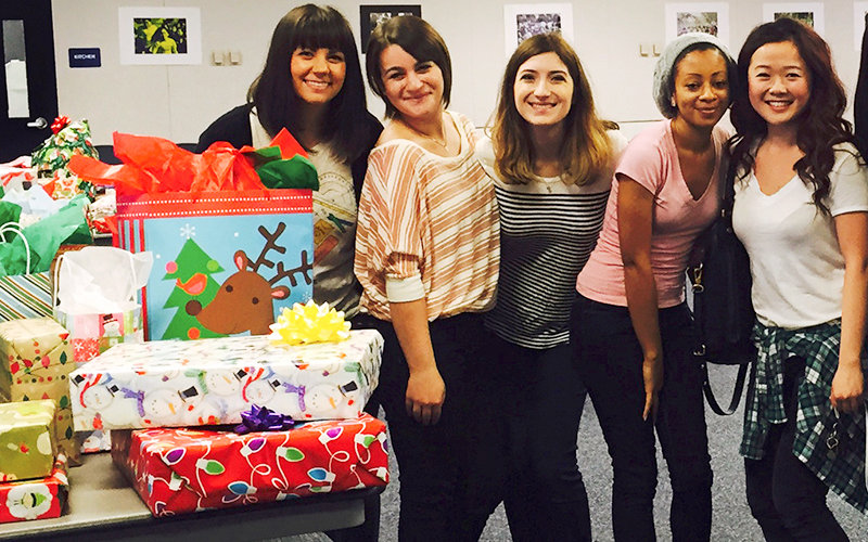 smiling women in a classroom with holiday wrapped gifts