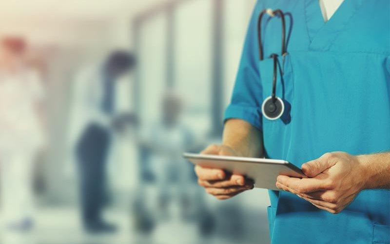 Doctor holds tablet.