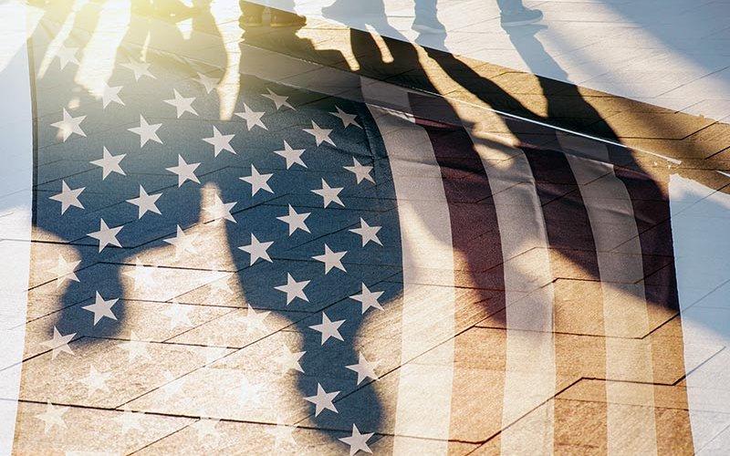 Human shadows behind American flag