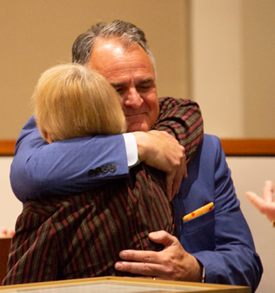 President Virjee and Marge Gordon embrace