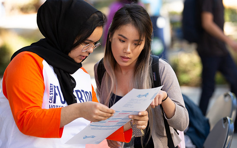 Maisune Abu-Elhaija helps register Leann Dinh.
