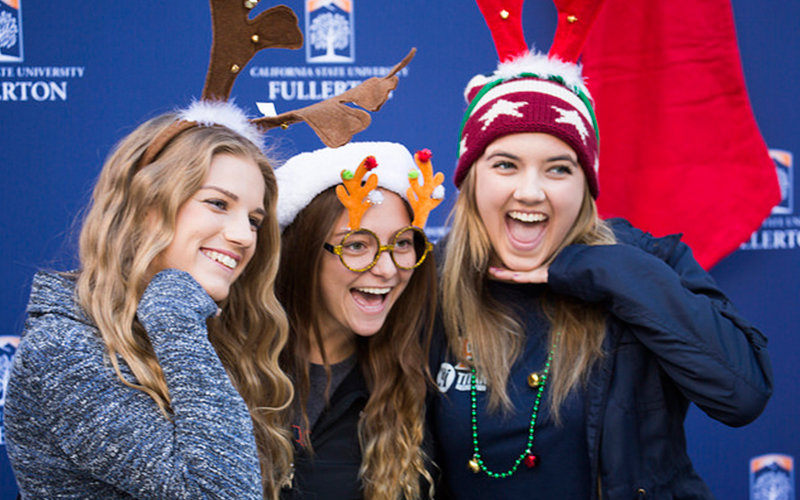 group of students dressed in holiday hats smiling