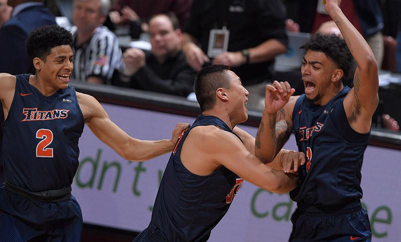 Titans basketball players cheer upon winning NCAA championship.