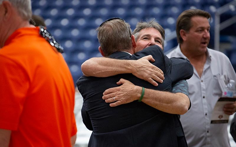 Tom Thomas '86 embraces a friend.