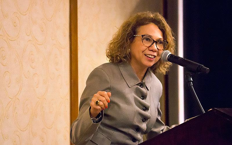 CSUF President Mildred Garcia speaking at a podium.