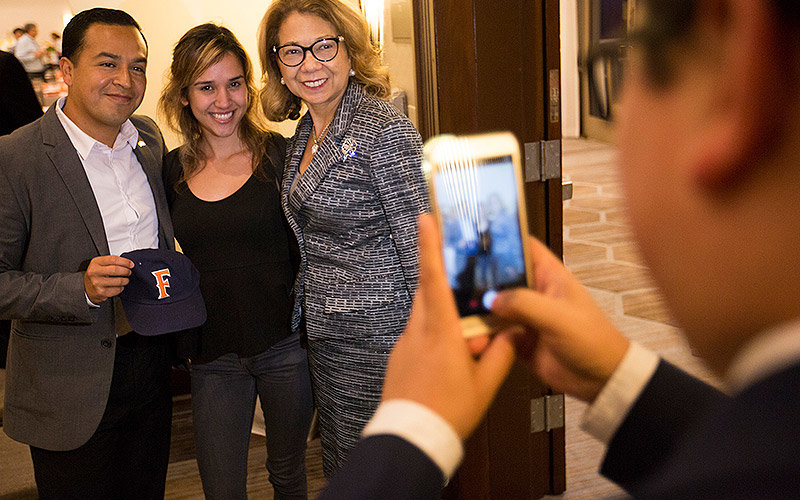 Student business major Areli Sena, center, poses for a photo with keynote speaker Cesar Vargas and CSUF President Mildred García.