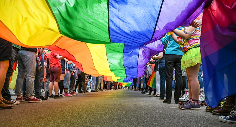 Youth raising the LGBTQ flag.