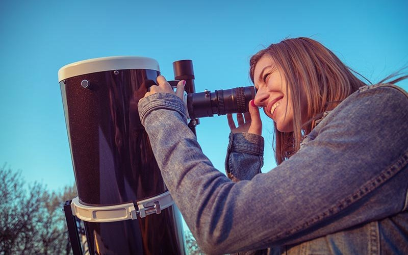 Young women looking through telescope