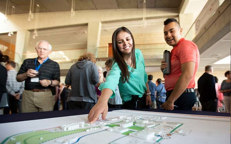 CSUF Housing Community Coordinator Jennifer Ortiz interacts with facsimiles of campus buildings in the Master Plan.