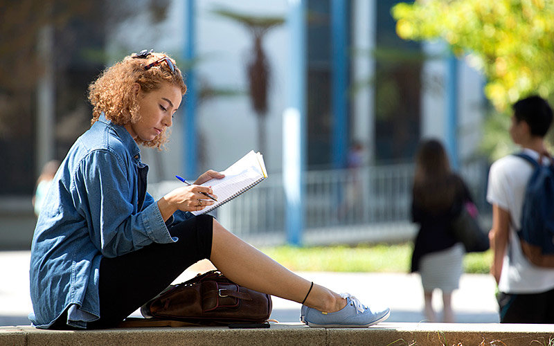 Female student studying outdoors.