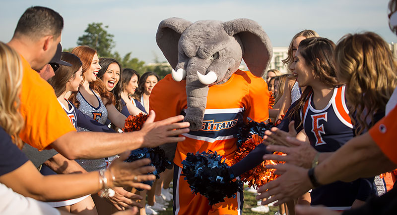 Tuffy receiving high fives during Homecoming.
