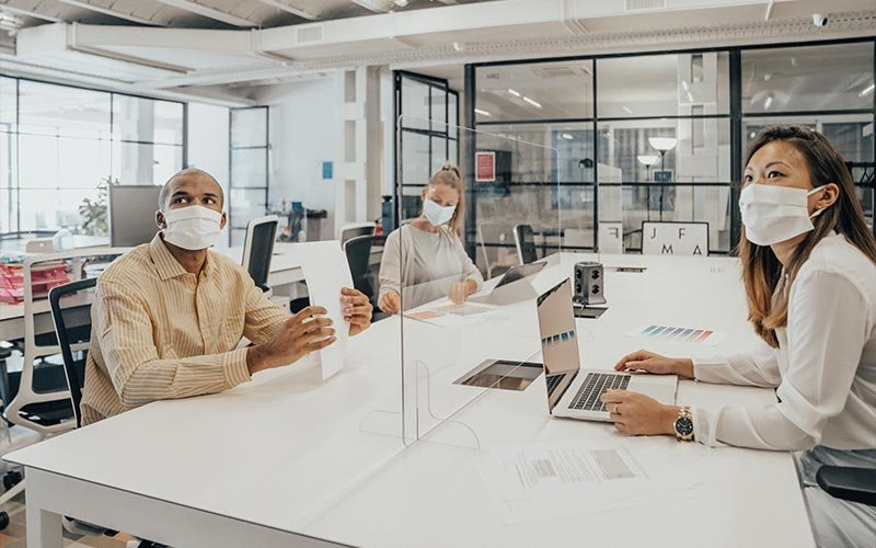 People wearing masks working in an office with glass partition dividing them