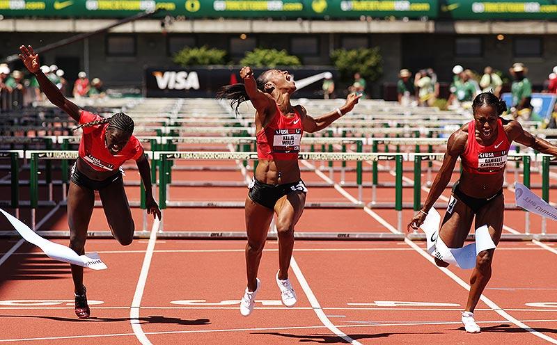 Female track athletes reaching the finish line