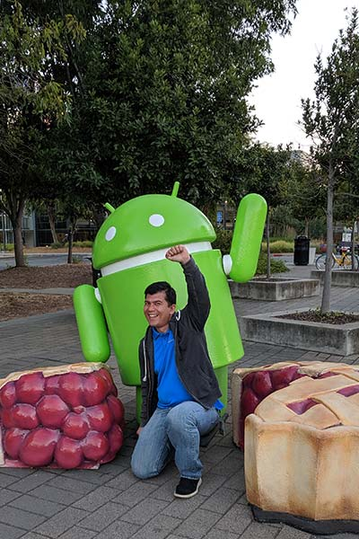 Paul Inventado poses in front of Android statue
